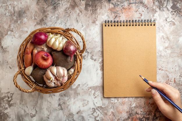 Draufsichtkorb mit gemüse, knoblauch, zwiebeln und rüben auf heller reife salatdiätfarbe