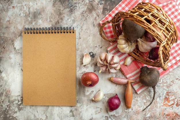 Draufsichtkorb mit gemüse, knoblauch, zwiebeln und rüben auf leichtem rohem fotodiät-farbsalat
