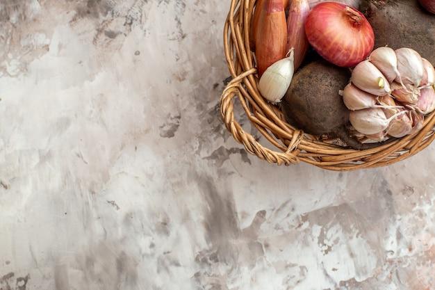Draufsichtkorb mit gemüseknoblauchzwiebeln und -rüben auf hellem reifem salatfotodiätfreiraum