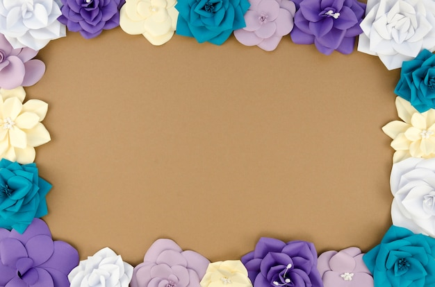 Draufsichtkreisrahmen mit papierblumen und braunem hintergrund