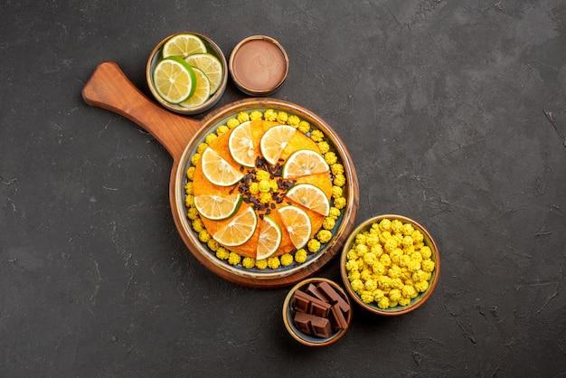 Draufsichtkuchen an bord bonbons schokoladencreme und geschnittene limetten in schalen und orangenkuchen auf dem schneidebrett auf dem tisch