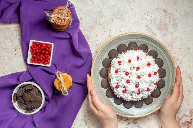 Draufsichtkuchen auf teller in frauenhandplätzchen, die mit seilschüsseln mit beeren und schokolade auf violettem schal gebunden sind