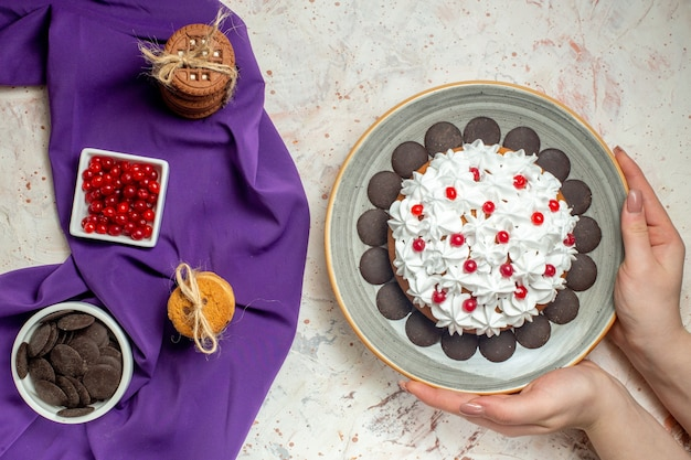 Draufsichtkuchen auf teller in weiblichen handplätzchen, die mit seilschüsseln mit beeren und schokolade auf violettem schal gebunden sind