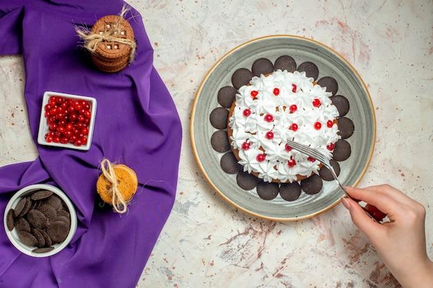 Draufsichtkuchen auf tellerplätzchen, die mit seilschüsseln mit beeren und schokolade auf lila schalgabel in frauenhand gebunden sind