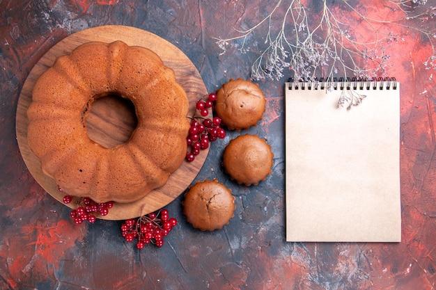 Draufsichtkuchen ein kuchen mit roten johannisbeeren die appetitlichen cupcakes neben dem weißen notizbuch