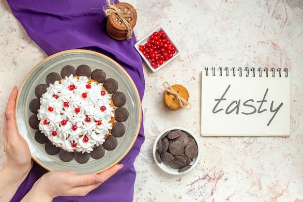 Draufsichtkuchen mit gebäckcreme auf grauem ovalem teller in der hand der frau. leckeres wort auf notizbuch auf weißem tisch geschrieben