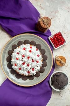 Draufsichtkuchen mit gebäckcreme auf grauem teller lila schalkekse mit seilbeeren und schokolade in schalen gebunden