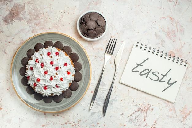 Draufsichtkuchen mit gebäckcreme auf ovaler plattenschokolade in schüsselgabel und -messer. leckeres wort auf notizbuch geschrieben