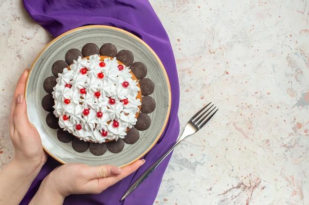 Draufsichtkuchen mit gebäckcreme auf teller in der weiblichen hand lila schalgabel auf grauem tisch