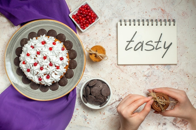 Draufsichtkuchen mit gebäckcreme auf teller lila schalbeeren und schokolade in schalen gebundene kekse in weiblicher hand auf weißem tisch