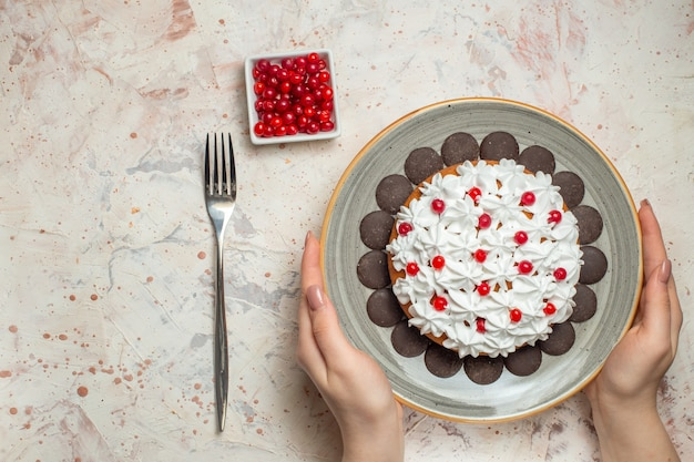Draufsichtkuchen mit gebäckcreme und schokolade in weiblicher handbeere in schüsselgabel