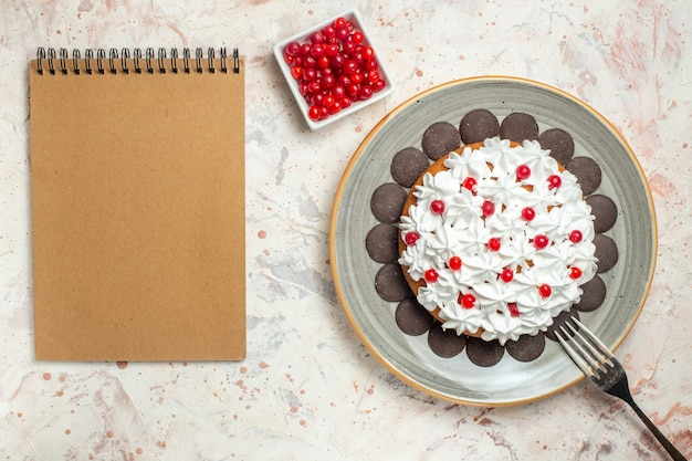 Draufsichtkuchen mit gebäckcreme und schokoladenbeere im schüsselgabelnotizbuch