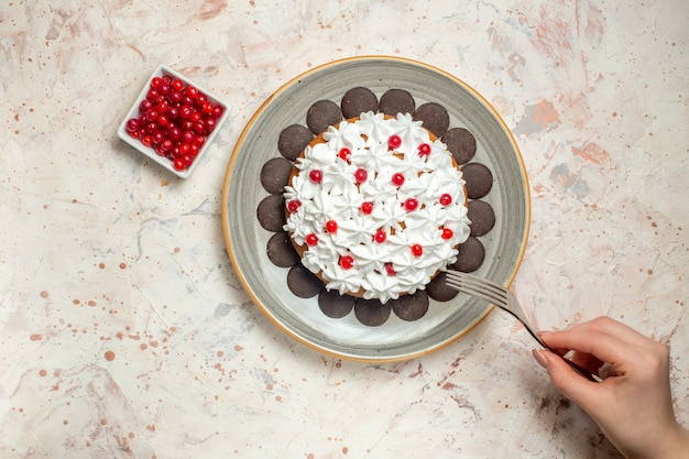 Draufsichtkuchen mit gebäckcreme und schokoladenbeeren in schüsselgabel in weiblicher hand
