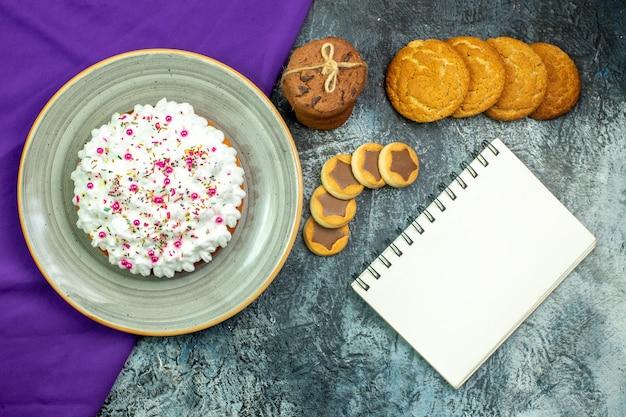 Draufsichtkuchen mit gebäckcreme-violetten schalkeksen, die mit seilkeksen-notizblock auf grauem hintergrund gebunden sind