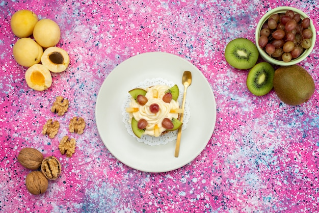Draufsichtkuchen mit sahne- und fruchtscheiben zusammen mit aprikosen und kiwis auf der farbigen hintergrundkuchenkeks-süßen zuckerfarbe