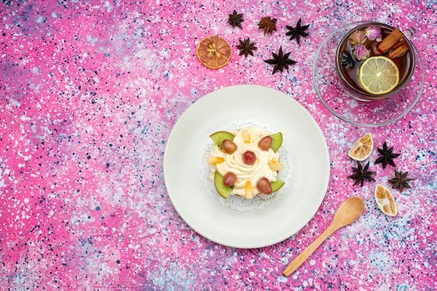 Draufsichtkuchen mit sahne- und fruchtscheiben zusammen mit tee auf der farbigen hintergrundkuchenkeks-süßen zuckerfarbe
