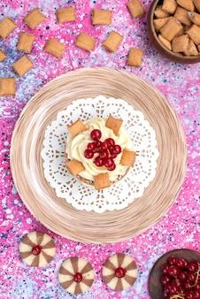 Draufsichtkuchen mit sahne zusammen mit keksen und preiselbeeren auf der bunten hintergrundkuchenbiskuitzuckersüße farbe