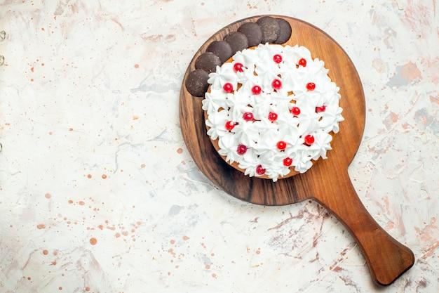 Draufsichtkuchen mit schokolade und weißer gebäckcreme auf hölzernem schneidebrett