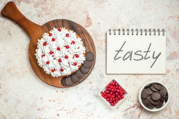 Draufsichtkuchen mit weißer gebäckcreme auf hölzernem schneidebrett lecker auf notizbuch geschrieben