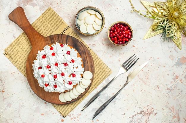 Draufsichtkuchen mit weißer gebäckcreme auf holzbrett auf zeitung. weihnachtsschmuck
