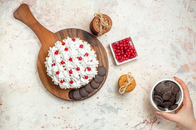 Draufsichtkuchen mit weißer gebäckcreme auf schneidebrettschüssel mit beerenschokoladenschüssel in weiblichen handplätzchen, die mit seil auf hellgrauem tisch gebunden sind