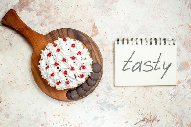 Draufsichtkuchen mit weißer gebäckcreme und schokolade auf hölzernem schneidebrett lecker auf notizbuch geschrieben