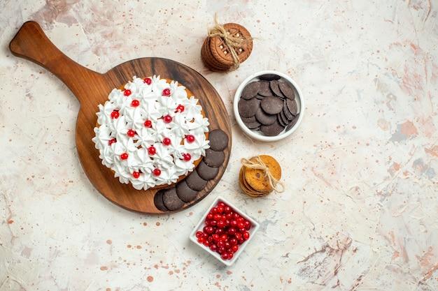 Draufsichtkuchen mit weißer gebäckcreme und schokolade auf schneidebrettschalen mit beeren und schokoladenkeksen mit seil gebunden tied