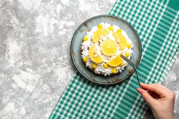 Draufsichtkuchen mit weißer gebäckcreme und zitronenscheiben auf rundem teller auf grün-weiß karierter tischtuchgabel in weiblicher hand