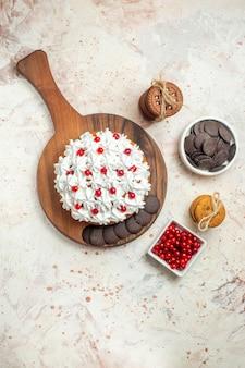 Draufsichtkuchen mit weißer sahne auf schneidebrettschüsseln mit beeren und schokoladenkeksen, die mit einem seil auf grauem tisch gebunden sind