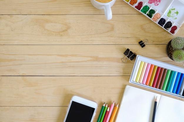Draufsichtkünstlerarbeitsplatz smartphone, farbe, becher kaffee, notizblockpapier, kaktus und bleistift auf holztisch
