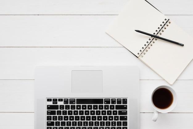 Draufsichtlaptop mit kaffee und notizbuch