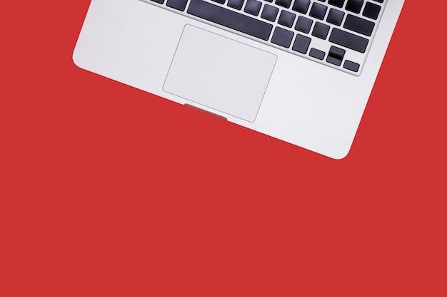 Draufsichtlaptophintergrund und exemplarplatz auf rotem hintergrund, rotes schreibtischbüro mit laptop