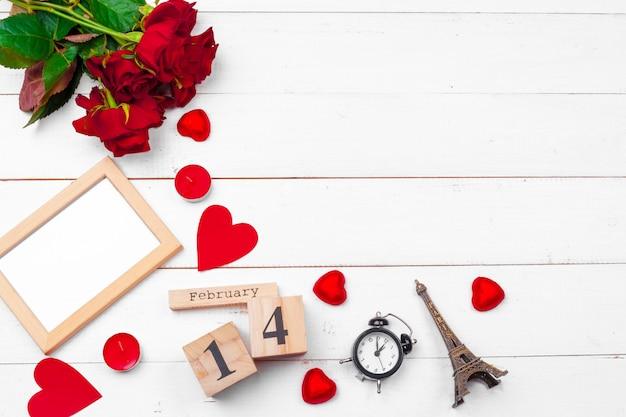 Draufsichtliebesfeiertagsfeier kreative valentine day-romantische zusammensetzungsebenenlage roter herzkalender-datumsweißer hölzerner hintergrund
