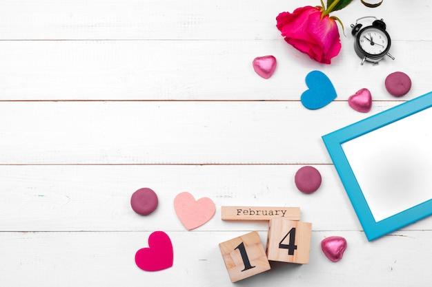 Draufsichtliebesfeiertagsfeier kreative valentine day-romantische zusammensetzungsebenenlage roter herzkalenderdatum weißer hölzerner hintergrund