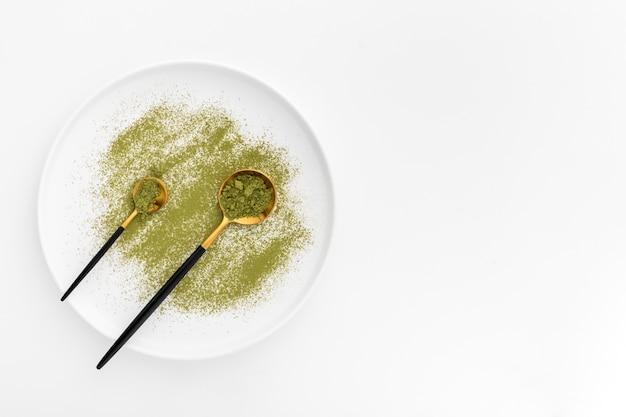 Draufsichtlöffel mit matcha pulver auf einer platte