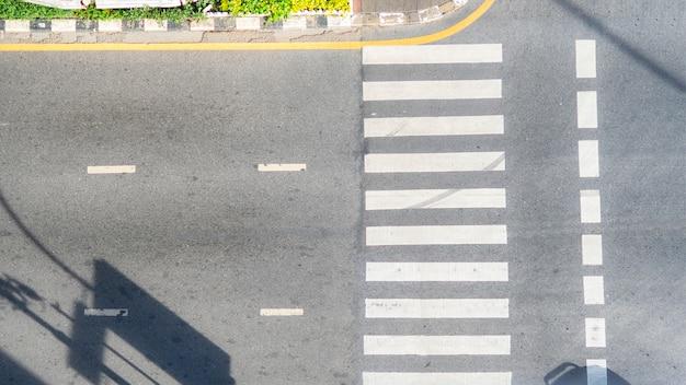 Draufsichtluftfoto der asphaltbahn und des fußgängerzebrastreifens in der verkehrsstraße mit licht- und schattenschattenbild