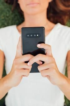 Draufsichtmädchen, das modernes telefon anhält
