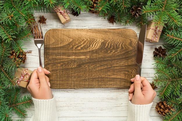 Draufsichtmädchen hält gabel und messer in der hand und ist essfertig. leere hölzerne rechteckige platte auf hölzernem weihnachten. feiertagsabendessenteller mit dekor des neuen jahres