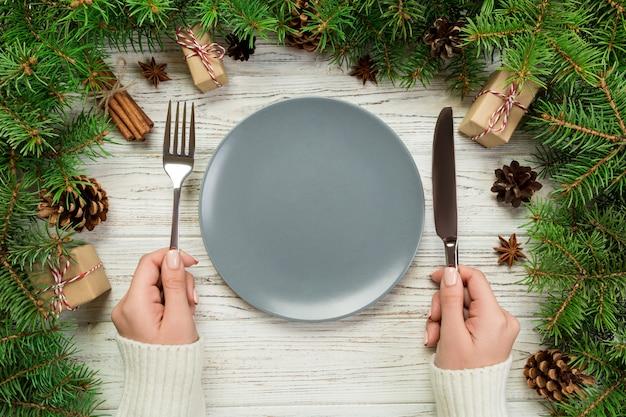 Draufsichtmädchen hält gabel und messer in der hand und ist essfertig. rundes keramisches der leeren platte auf hölzernem weihnachten. feiertagsessengericht mit dekor des neuen jahres