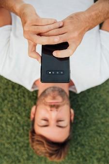 Draufsichtmann auf dem gras, das mobiltelefon hält