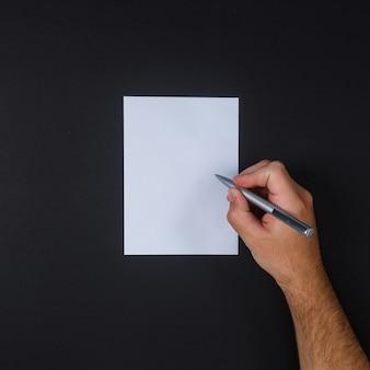 Draufsichtmann, der auf papier mit stift auf schwarzem hintergrund schreibt.