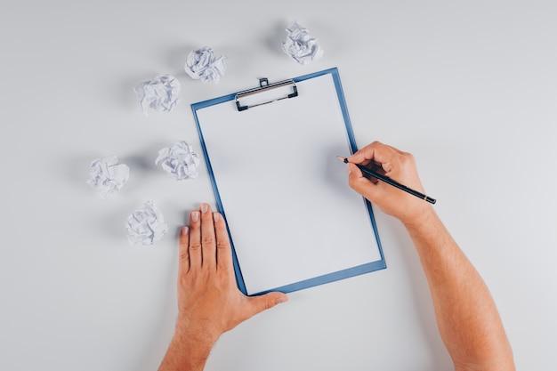Draufsichtmann, der auf zwischenablage mit zerknitterten papieren auf weiß schreibt