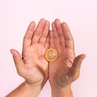 Draufsichtmann, der ein transparentes kondom hält