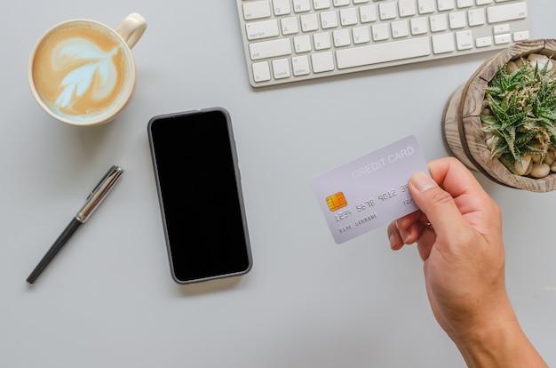 Draufsichtmann, der eine kreditkarte auf dem schreibtisch hält. computer, kaffee, stift und smartphone. online-shopping-geschäft, mit kreditkarte bezahlen