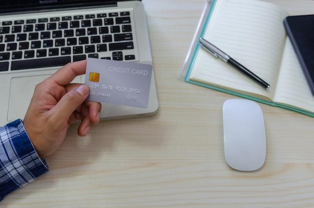 Draufsichtmann, der eine kreditkarte hält und ein blaues kariertes hemd auf dem schreibtisch trägt. laptop computer notizblock und stift. online-shopping-geschäft, mit kreditkarte bezahlen