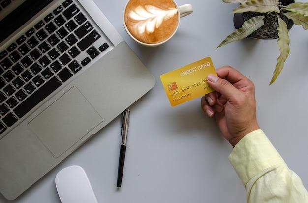 Draufsichtmann, der eine kreditkarte und auf dem schreibtisch hält. laptop computer notizblock und stift. online-shopping-geschäft, mit kreditkarte bezahlen