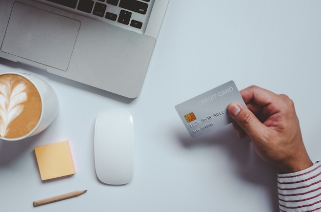 Draufsichtmann, der eine kreditkarte und auf dem schreibtisch hält. laptop-computer notizblock und stift