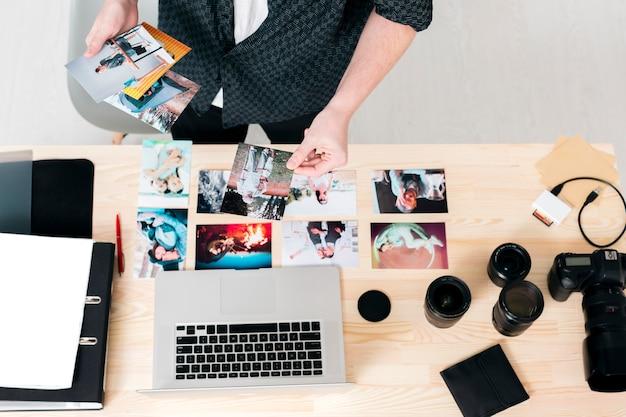 Draufsichtmann, der mit fotos und laptop arbeitet