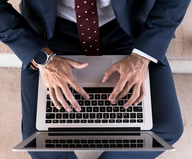 Draufsichtmann in der klage, die an laptop arbeitet