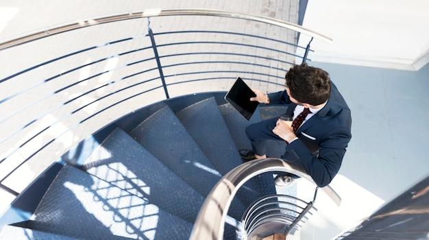 Draufsichtmann mit der tablette, die auf treppe steht